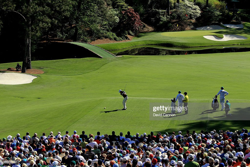 Phil Mickelson plays his tee shot on the 12th hole while YE Yang of Korea looks on during the third round of the 2010 Masters Tournament at Augusta...