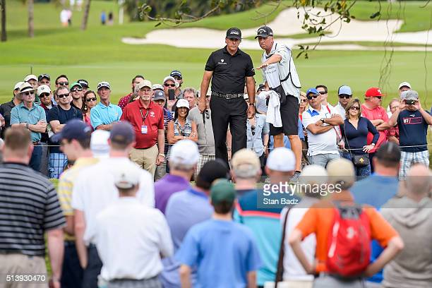 Phil Mickelson reads his putt with caddie Jim 'Bones' Mackay on the seventh hole green as fans watch during the third round of the World Golf...