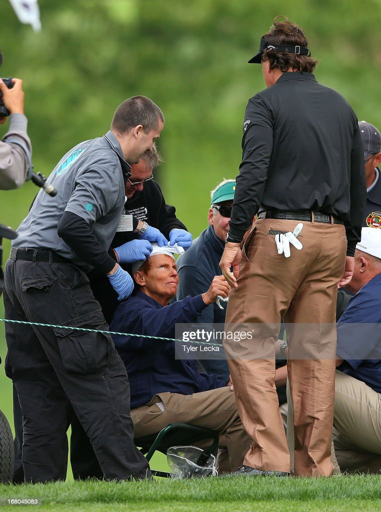 Phil Mickelson shakes hands with a patron who was hit by his ball on the 14th hole during the third round of the Wells Fargo Championship at Quail Hollow Club on May 4, 2013 in Charlotte, North Carolina.