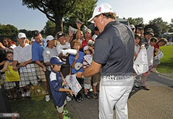 Phil Mickelson signs autographs for fans during the third round of the World Golf ChampionshipsBridgestone Invitational at Firestone Country Club on...