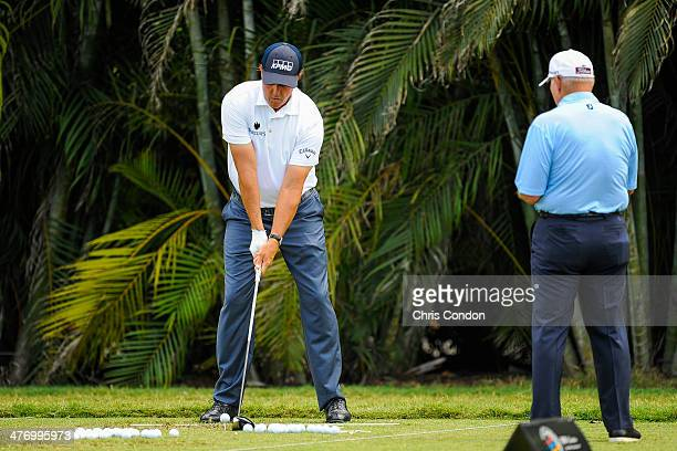 Phil Mickelson speaks with golf instructor Butch Harmon on the practice range during the first round of the World Golf ChampionshipsCadillac...