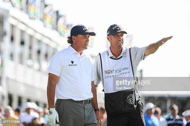 Phil Mickelson speaks with his caddie Jim 'Bones' Mackay before teeing off on the 10th hole during the second round of the World Golf...