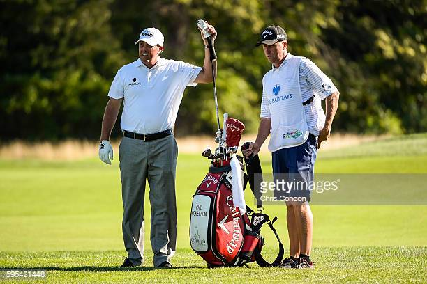 Phil Mickelson takes a club out of his bag with caddie Jim 'Bones' Mackay on the 12th hole during the first round of The Barclays at Bethpage State...