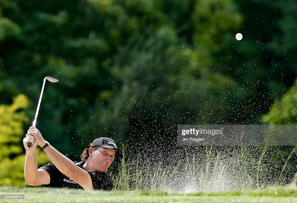 Phil Mickelson takes his shot out of the bunker on the eighth hole during the first round of the Deutsche Bank Championship at the TPC Boston on...