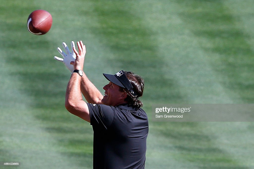 Phil Mickelson throws a football to the crowd on the 16th hole during the third round of the Waste Management Phoenix Open at TPC Scottsdale on...