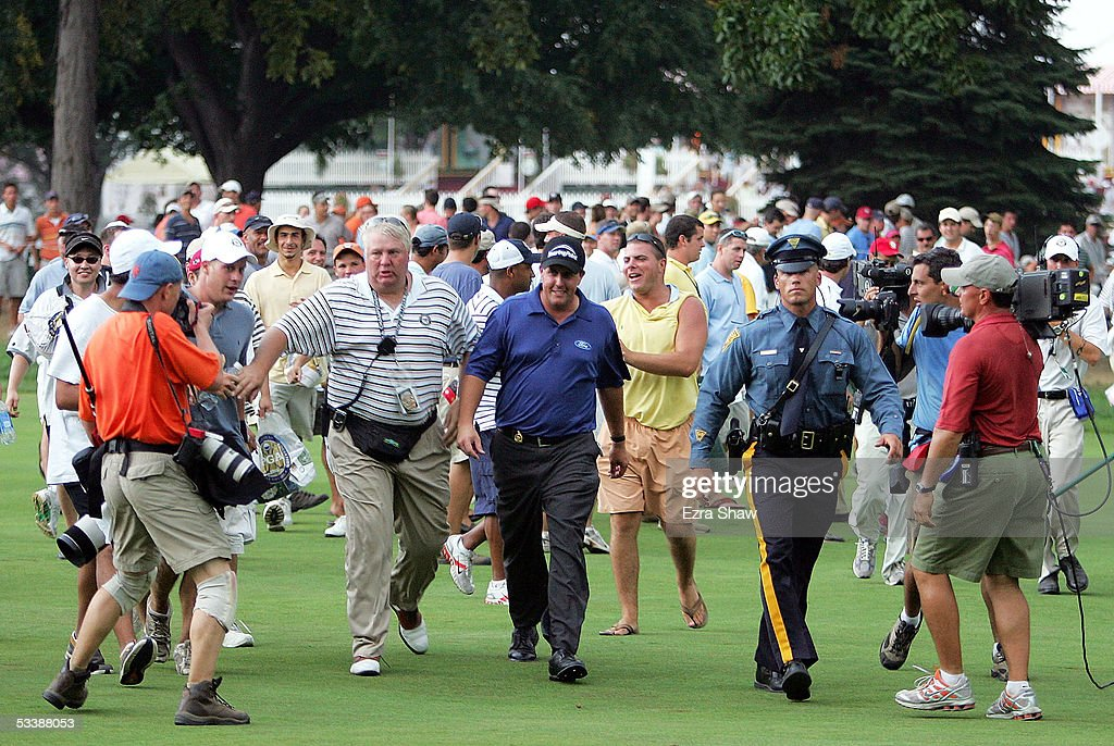 Phil Mickelson (C) walks in off the 14th hole after play was suspended due to weather during the final round of the 2005 PGA Championship on August 14, 2005 at Baltusrol Golf Club in Springfield, New Jersey.
