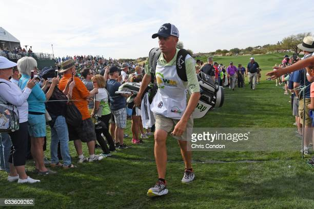 Phil Mickelson's caddie Jim 'Bones' MacKay walks off the 9th green during the first round of the Waste Management Phoenix Open at TPC Scottsdale on...