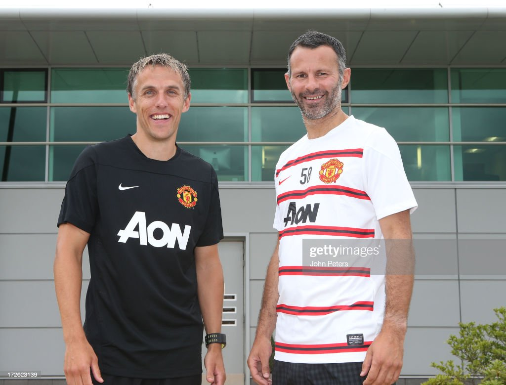 Phil Neville (L) and Ryan Giggs (R) of Manchester United pose after Neville was appointed first team coach and Giggs was appointed player/coach at the Aon Training Complex on July 4, 2013 in Manchester, England.