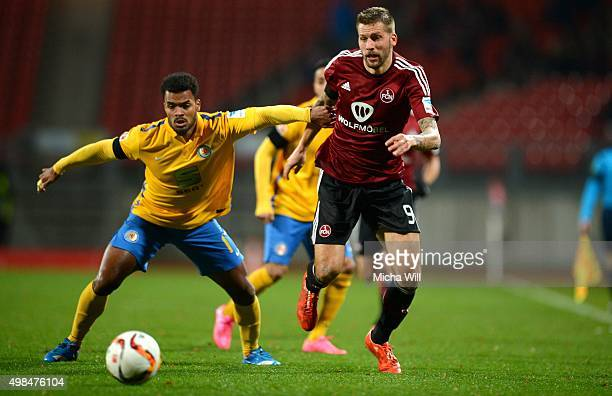 Phil OfosuAyeh of Braunschweig is challenged by Guido Burgstaller of Nuernberg during the Second Bundesliga match between 1 FC Nuernberg and...