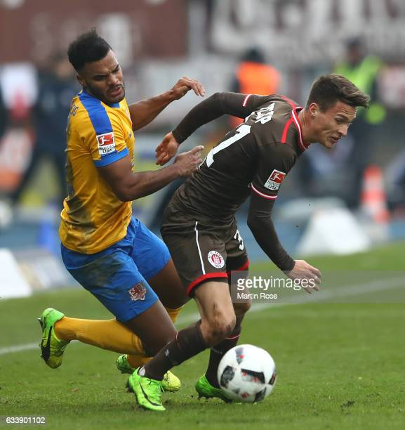 Phil OfosuAyeh of Braunschweig is challenged by Maurice Jerome Litka of St Pauli during the Second Bundesliga match between Eintracht Braunschweig...