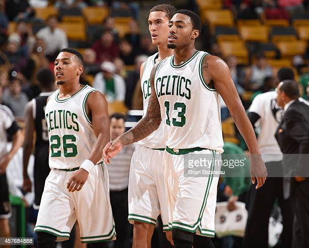 Phil Pressey Dwight Powell and James Young of the Boston Celtics walk toward the sidelines during the game against the Brooklyn Nets on October 22...