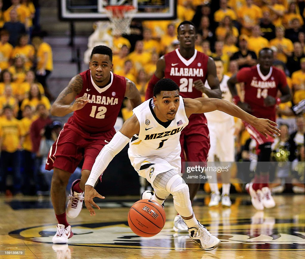 Phil Pressey #1 of the Missouri Tigers controls the ball on a fast break as Trevor Releford #12; Rodney Cooper #21, and Moussa Gueye #14 of the Alabama Crimson Tide chase during the game at Mizzou Arena on January 8, 2013 in Columbia, Missouri.