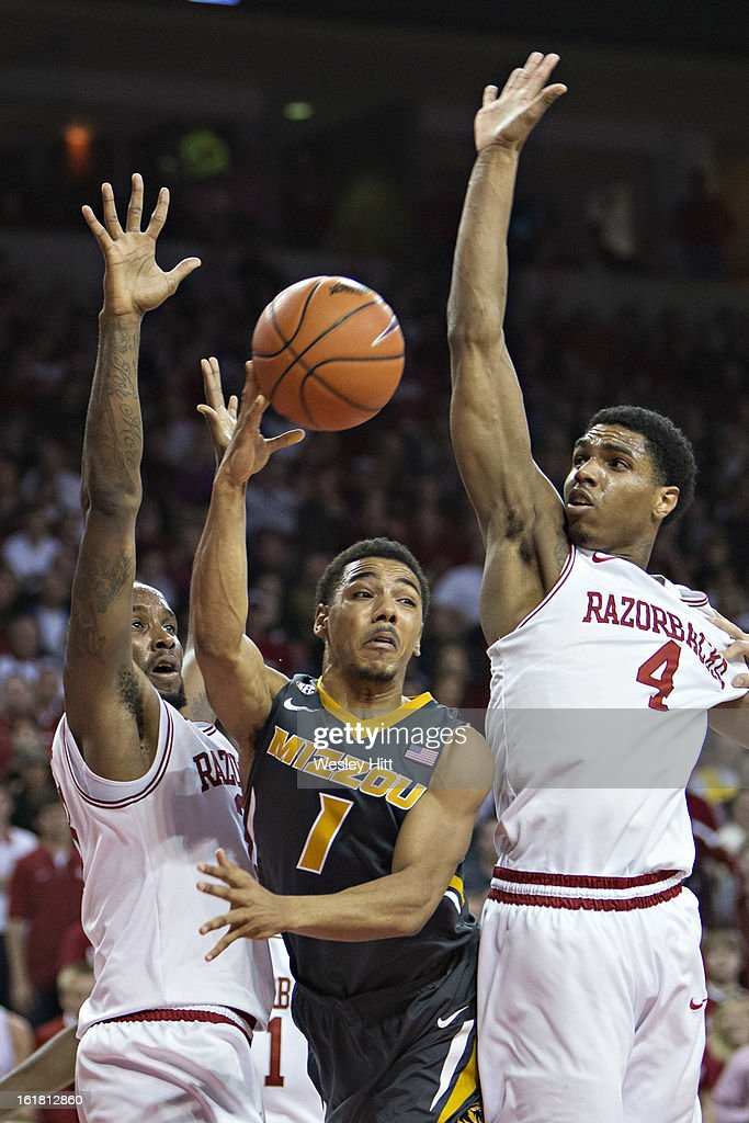 Phil Pressey #1 of the Missouri Tigers makes a pass between Coty Clarke #4 and Marshawn Powell #33 of the Arkansas Razorbacks at Bud Walton Arena on February 16, 2013 in Fayetteville, Arkansas. The Razorbacks defeated the Tigers 73-71.