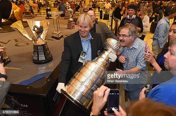 Phil Pritchard Hockey Hall of Fame curator also known as the keeper of the Stanley Cup poses with a fan and the Stanley Cup at the MGM Grand Hotel...