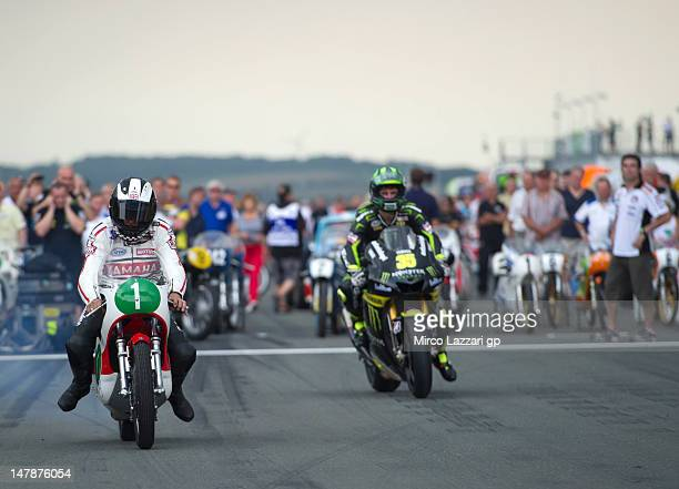 Phil Read of Great Britain and Cal Crutchlow of Great Britain and Monster Yamaha Tech 3 rides the bikes on the grid during the preevent 'MotoGP...