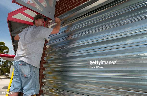 Phil Reilly works to cover windows of a restaurant August 12 2004 in Ft Myers Florida This Gulf Coast community is bracing for Hurricane Charley as...