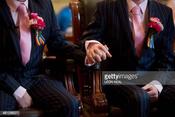 Phil Robathan and James Preston hold hands during their wedding ceremony in Brighton southern England on March 29 2014 Gay couples across England and...