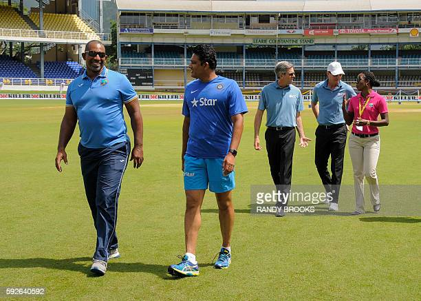 Phil Simmons head coach of West Indies and Anil Kumble head coach of India walks off the field after the pitch inspection by umpires Nigel Llong and...
