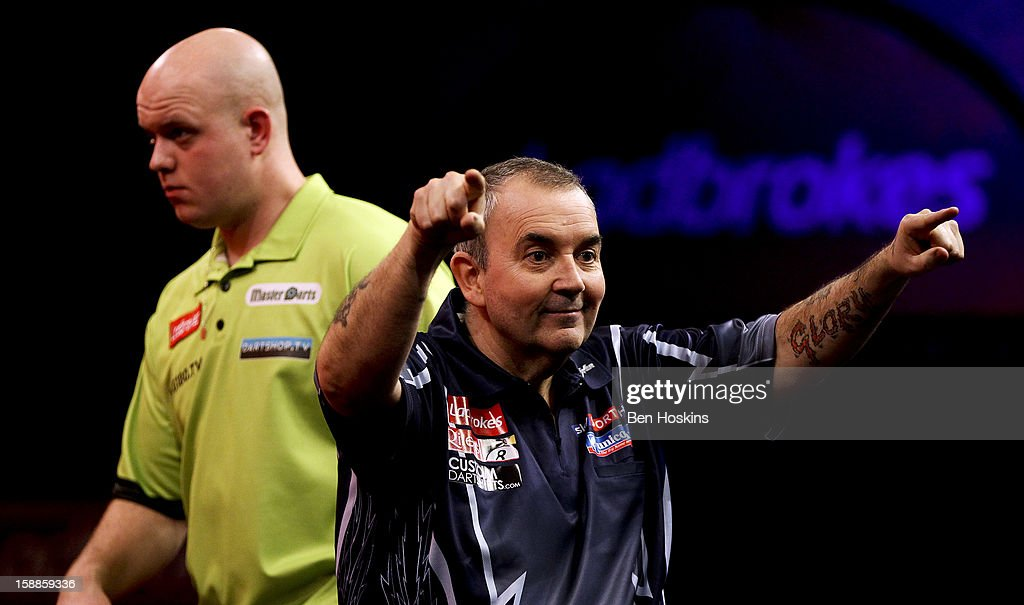 Phil Taylor celebrates winning the tenth set as Michael van Gerwen of the Netherlands looks on during the final of the 2013 Ladbrokes.com World Darts Championship at the Alexandra Palace on January 1, 2013 in London, England.
