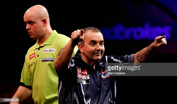 Phil Taylor celebrates winning the tenth set as Michael van Gerwen of the Netherlands looks on during the final of the 2013 Ladbrokescom World Darts...