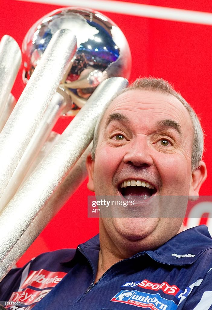 Phil Taylor of Britain celebrates with the Sid Waddell trophy after defeating Michael van Gerwen of the Netherlands in the PDC World Championship darts final against at Alexandra Palace in north London on January 1, 2013. Taylor ended up winning the match 7 sets to 4. AFP PHOTO/Leon Neal