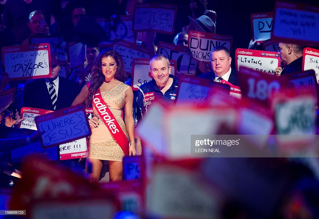 Phil Taylor of Britain (C) prepares to take part in the PDC World Championship darts final against Michael van Gerwen of the Netherlands, at Alexandra Palace in north London on January 1, 2013. AFP PHOTO/Leon Neal