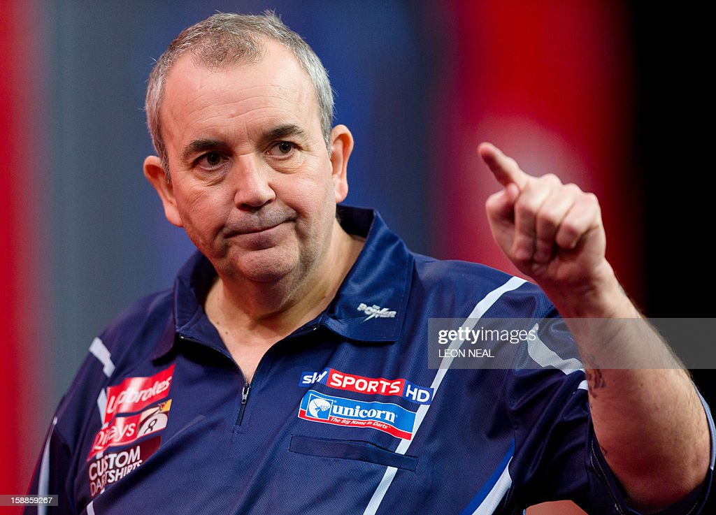 Phil Taylor of Britain reacts as he takes part in the PDC World Championship darts final against Michael van Gerwen of the Netherlands, at Alexandra Palace in north London on January 1, 2013. AFP PHOTO/Leon Neal