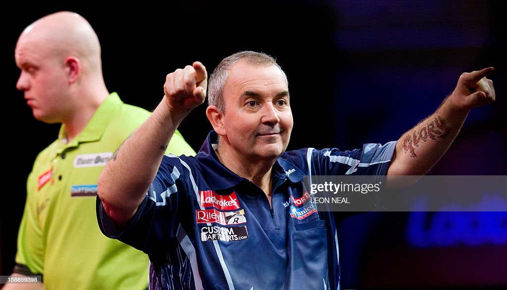 Phil Taylor of Britain (R) reacts as he takes part in the PDC World Championship darts final against Michael van Gerwen (L) of the Netherlands, at Alexandra Palace in north London on January 1, 2013. AFP PHOTO/Leon Neal