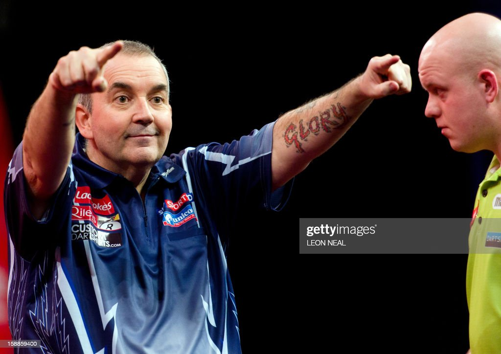 Phil Taylor of Britain (L) reacts as he takes part in the PDC World Championship darts final against Michael van Gerwen (R) of the Netherlands, at Alexandra Palace in north London on January 1, 2013. AFP PHOTO/Leon Neal