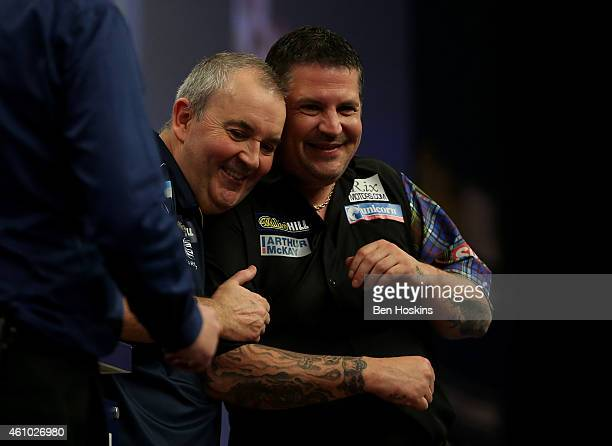 Phil Taylor of England and Gary Anderson of Scotland share a joke following the final of the 2015 William Hill PDC World Darts Championships at...