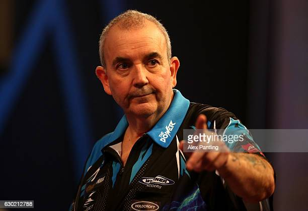 Phil Taylor of England celebrates victory following his first round match against David Platt of England during Day Four of the 2017 William Hill PDC...