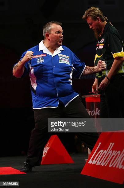 Phil Taylor of England celebrates winning a crucial set in the game against Simon Whitlock of Australia during the Final of the Ladbrokescom World...