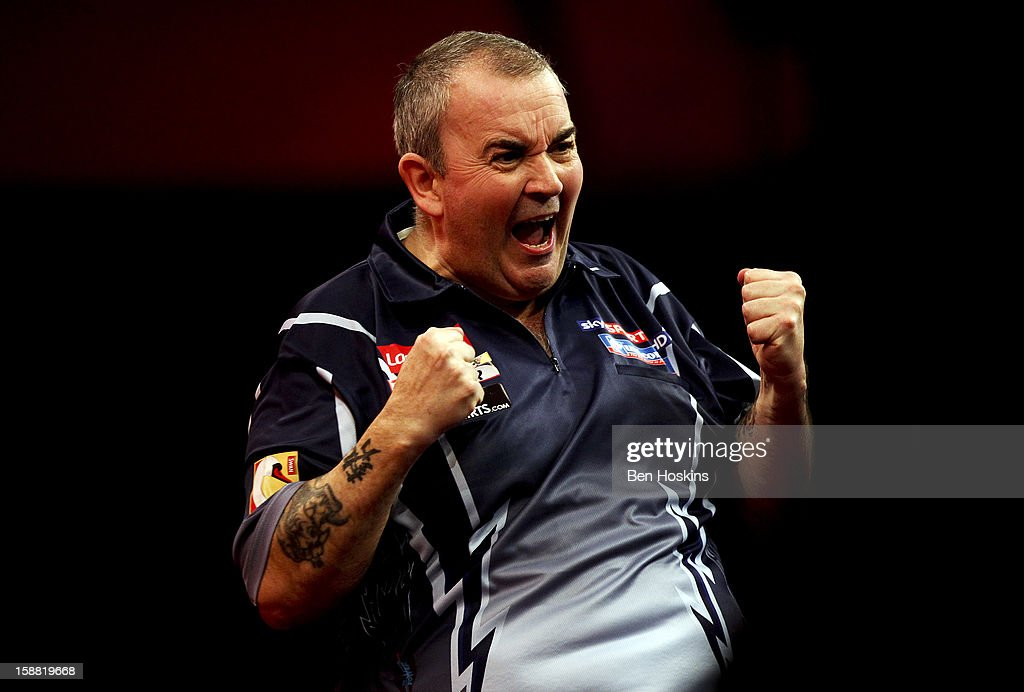 Phil Taylor of England celebrates winning the third set during his semi final match against Raymond van Barneveld of the Netherlands on day fourteen of the 2013 Ladbrokes.com World Darts Championship at the Alexandra Palace on December 30, 2012 in London, England.