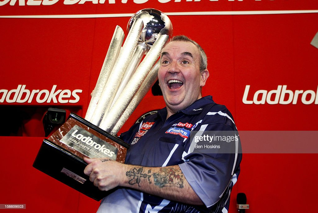Phil Taylor of England celebrates with the trophy after winning the final of the 2013 Ladbrokescom World Darts Championship at the Alexandra Palace...