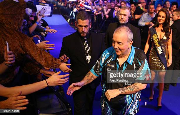 Phil Taylor of England greets supporters prior to his first round match against David Platt of England during Day Four of the 2017 William Hill PDC...
