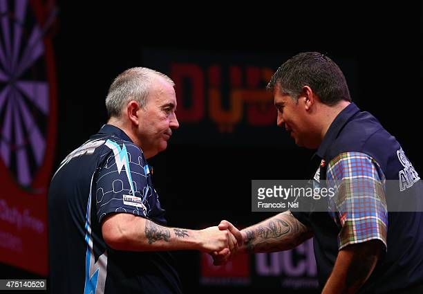 Phil Taylor of England is congratulated by Gary Anderson of Scotland after winning the 2015 Dubai Duty Free Darts Masters SemiFinal match at Dubai...