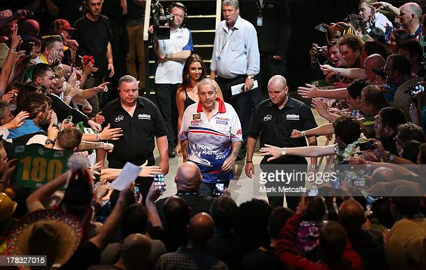 Phil Taylor of England walks out for his first round match against Kyle Anderson of Australia during the Sydney Darts Masters at Luna Park on August...