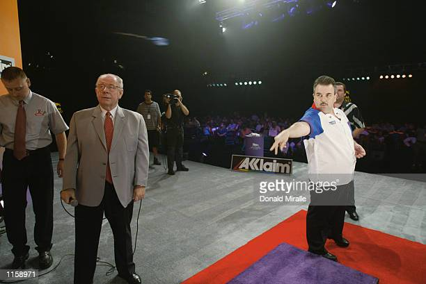 Phil Taylor of Great Britain throws his victory over Ronnie Baxter in the men's finals of the Desert Classic Darts Championships at the MGM Grand...