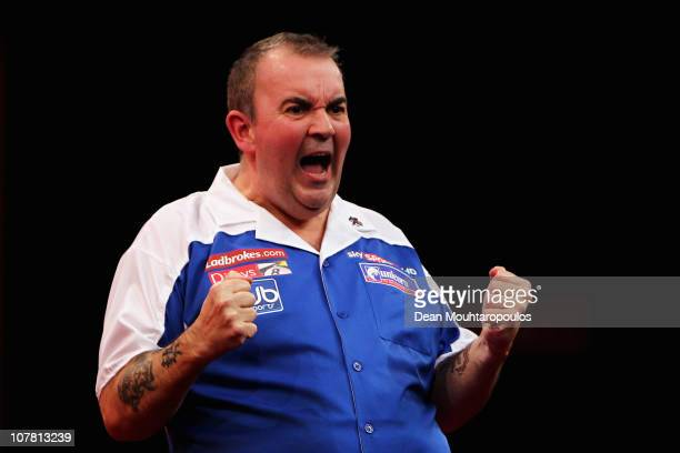Phil 'The Power' Taylor of England celebrates his win against Peter Wright of England during day 11 in the 2011 Ladbrokescom World Darts Championship...