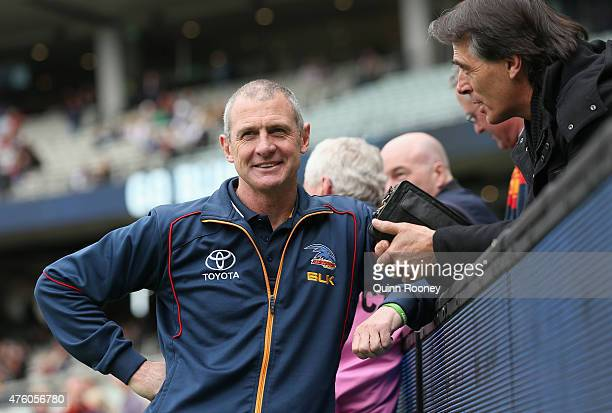 Phil Walsh the coach of the Crows talks to a spectator in the crowd during the round 10 AFL match between the Carlton Blues and the Adelaide Crows at...