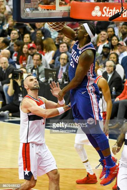 Philadelphia 76ers center Joel Embiid scores against Washington Wizards center Marcin Gortat on October 18 2017 at the Capital One Arena in...