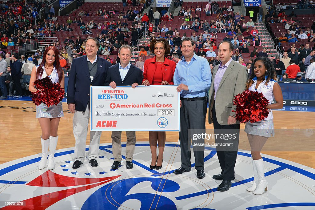 Philadelphia 76ers CEO & Co-Owner Adam Aron, Managing Owner Joshua Harris, Co-Managing Owner David Blitzer and ACME Vice President of Retail Dan Croce present Judge Renee Caldwell Hughes of the American Red Cross (center) with a check for the money raised through Operation Rebound, their Hurricane Sandy relief effort at the Wells Fargo Center on January 18, 2013 in Philadelphia, Pennsylvania.