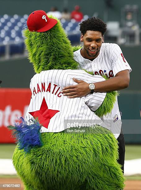 Philadelphia 76ers first round draft pick Jahlil Okafor gets a hug from the Philly Phanatic after he threw out the first pitch prior to the start of...