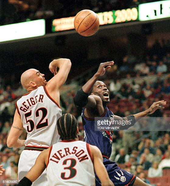 Philadelphia 76ers Matt Geiger slaps the ball away from the hands of the Toronto Raptors Kevin Willis as Allen Iverson looks on in tonight's game 14...