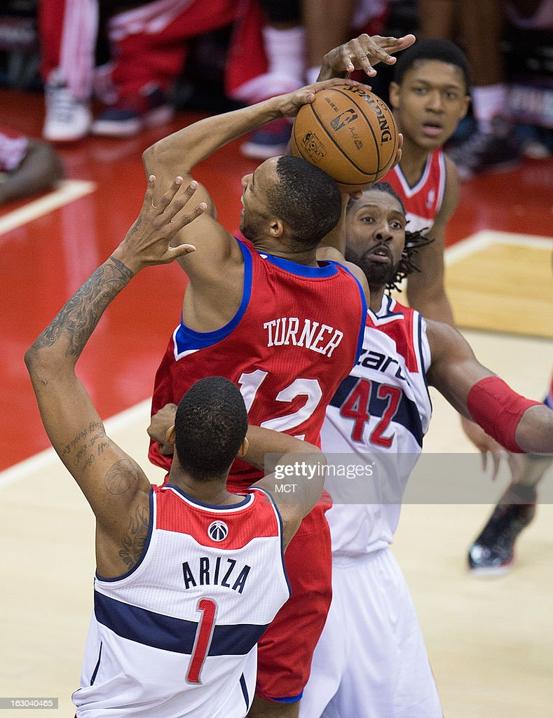 Philadelphia 76ers small forward Evan Turner (12) goes to the basket between Washington Wizards small forward Trevor Ariza (1) and center Nene (42) during the second half of their game played at the Verizon Center in Washington, D.C., Sunday, March 3, 2013. Washington defeated Philadelphia 90-87.