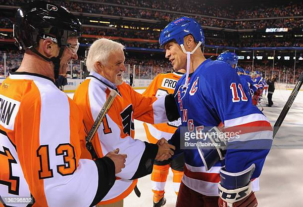 Philadelphia Flyers alumni goaltender Bernie Parent shakes hands with New York Rangers alumni Mark Messier after the Alumni game prior to the 2012...