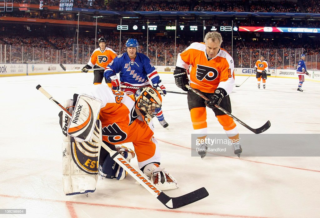 Philadelphia Flyers alumni goaltender Neil Little #35 covers the puck in front of teammate Joe Watson #14 and Brian Mullen #19 of the New York Rangers during the Alumni game prior to the 2012 Bridgestone NHL Winter Classic at Citizens Bank Park on December 31, 2011 in Philadelphia, Pennsylvania.