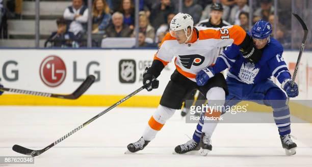 Philadelphia Flyers center Jori Lehtera holds Toronto Maple Leafs center Patrick Marleau at bay as he brings up the puck Toronto Maple Leafs VS...