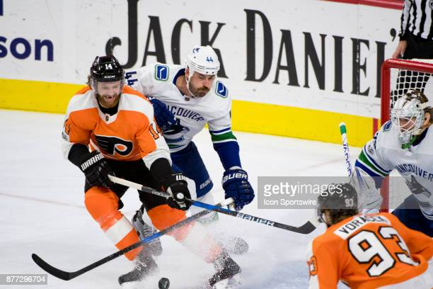 Philadelphia Flyers Center Sean Couturier and Vancouver Canucks Defenceman Erik Gudbranson watch a shot head towards the net in the third period...