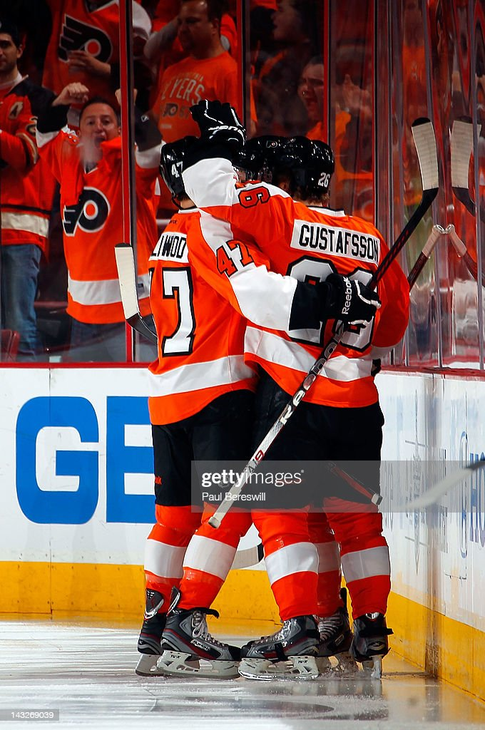 Philadelphia Flyers Eric Wellwood #47 and Erik Gustaffson #26 mob teammate Claude Giroux as fans cheer after Giroux scored a goal 32 seconds into the first period of Game Six of the Eastern Conference Quarterfinals against the Pittsburgh Penguins during the 2012 NHL Stanley Cup Playoffs at Wells Fargo Center on April 22, 2012 in Philadelphia, Pennsylvania. Flyers won the game 5-1 to eliminate the Penguins from the playoffs